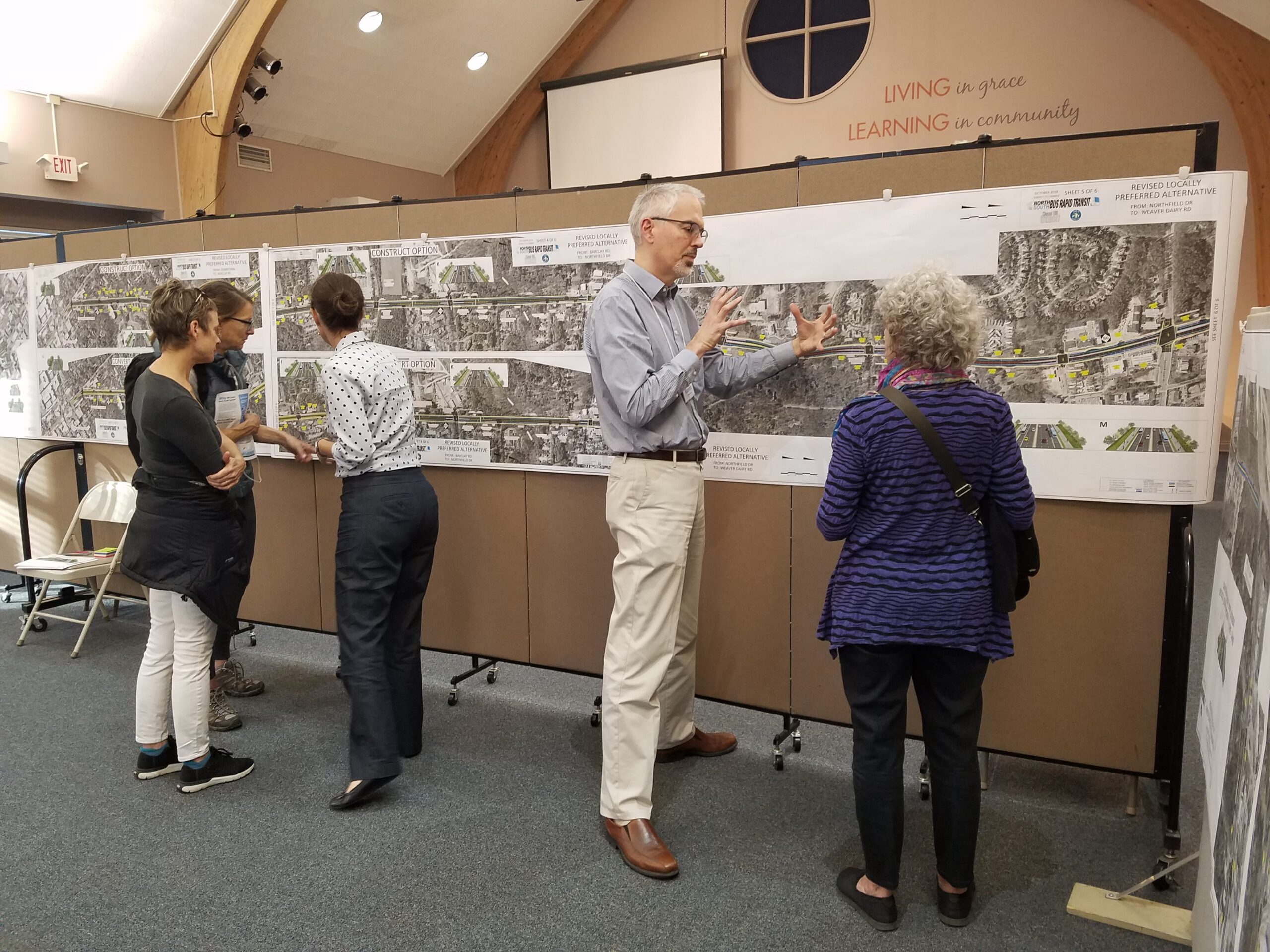 Project consultant reviewing a roadway design map with the public at Open House #2.