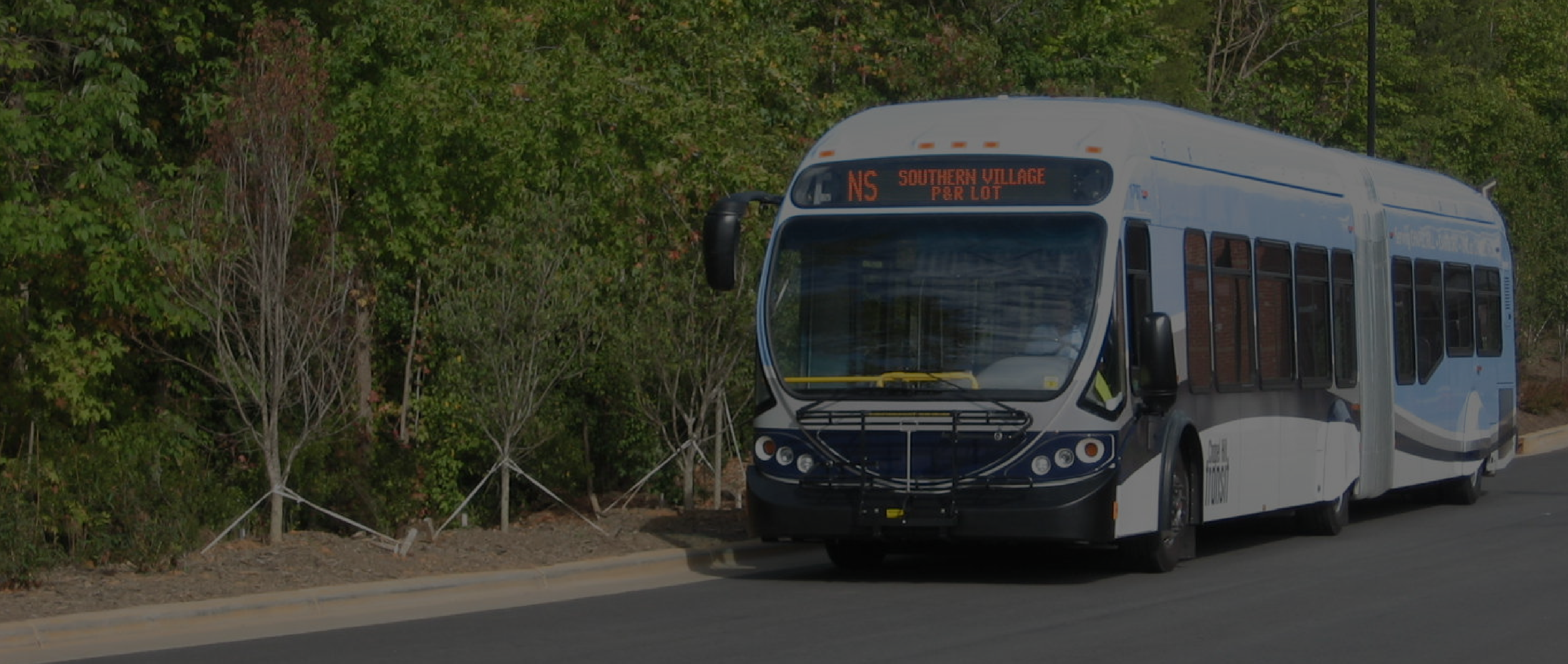 An articulated Chapel Hill Transit bus parked on the side of the road.