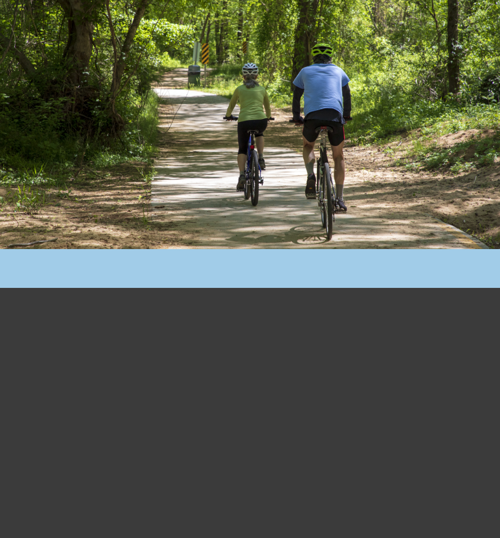 A couple bicycling on a forested trail in Chapel Hill.
